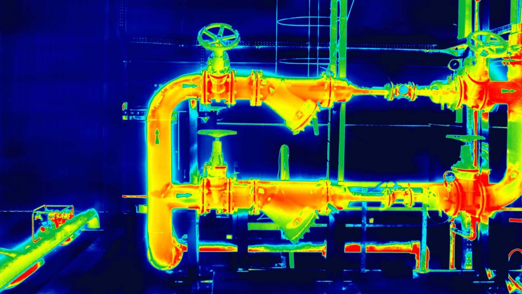 Drone thermal image shows heat from industrial pipes